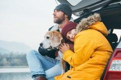 Padre e figlio con il cane del cane da lepre che colloca insieme nel tronco di automobile lat immagine stock