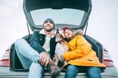 Padre e figlio con il cane del cane da lepre che colloca insieme nel tronco di automobile lon fotografia stock libera da diritti