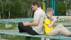 Padre e figlio con il computer e lo smartphone della compressa stock footage