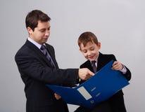 Padre e figlio con il dispositivo di piegatura Fotografie Stock Libere da Diritti