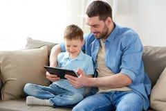 Padre e figlio con il pc della compressa che gioca a casa Immagine Stock