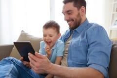 Padre e figlio con il pc della compressa che gioca a casa Fotografia Stock Libera da Diritti
