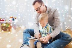 Padre e figlio con il pc della compressa che gioca a casa Fotografie Stock