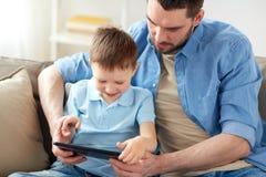 Padre e figlio con il pc della compressa che gioca a casa Fotografie Stock Libere da Diritti
