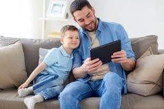 Padre e figlio con il pc della compressa che gioca a casa Fotografia Stock