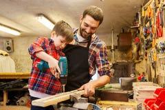 Padre e figlio con il trapano che funziona all'officina Immagini Stock Libere da Diritti