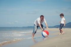 Padre e figlio con la palla che gioca a calcio sulla spiaggia al giorno immagini stock libere da diritti