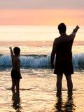 Padre e figlio davanti alla spiaggia del cielo di sera Immagine Stock