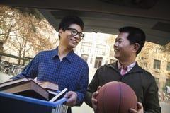 Padre e figlio dietro all'automobile davanti al dormitorio Fotografie Stock Libere da Diritti