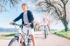 Padre e figlio divertendosi quando guidano le biciclette sulla strada campestre sotto gli alberi del fiore Immagine sportiva sana immagine stock libera da diritti
