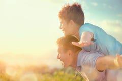 Padre e figlio felici divertendosi sopra il bello cielo all'aperto Fotografie Stock Libere da Diritti
