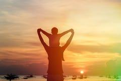 Padre e figlio felici sulla spiaggia di tramonto Immagine Stock