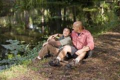 Padre e figlio ispanici del ritratto all'aperto dallo stagno fotografie stock libere da diritti