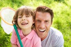 Padre e figlio nel campo con la rete dell'insetto fotografie stock
