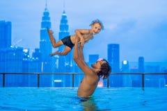 Padre e figlio nella piscina all'aperto con la vista della città in cielo blu immagine stock libera da diritti