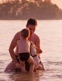 Padre e figlio in pieno intorno con il cane del cane da lepre nell'acqua di fiume fotografie stock libere da diritti