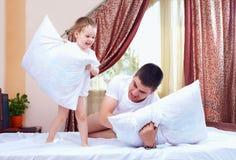 Padre e figlio positivi divertendosi a casa, lotta di cuscino immagine stock