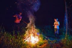 Padre e figlio, sottobosco bruciante dei paesani su fuoco alla notte, pulizia stagionale dell'area della campagna, stile di vita  immagine stock libera da diritti