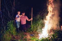 Padre e figlio, sottobosco bruciante dei paesani su fuoco alla notte, pulizia stagionale dell'area della campagna, stile di vita  fotografie stock libere da diritti