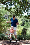Padre e figlio su un'oscillazione Fotografia Stock