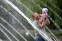 Padre e fondo vago figlia con i getti di acqua immagine stock