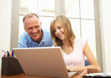 Padre e hija adolescente que usa la computadora portátil en el país Imagenes de archivo