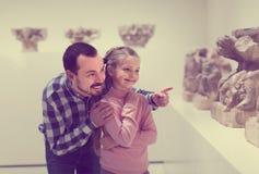 Padre e hija alegres con respecto a bajorrelieves clásicos en musa Imagen de archivo libre de regalías