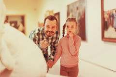 Padre e hija alegres con respecto a pinturas en museo Imagen de archivo libre de regalías