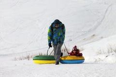 Padre e hija con el tubo de la nieve en día de invierno del sol Foto de archivo