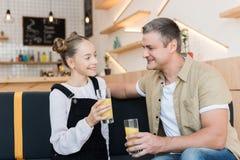 Padre e hija con el zumo de naranja Imagenes de archivo