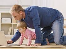 Padre e hija con la computadora portátil Fotografía de archivo libre de regalías