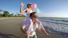 Padre e hija con los globos que juegan en la playa en el tiempo de la puesta del sol metrajes