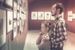 Padre e hija con respecto a la exposición de fotos en el museo Imagen de archivo