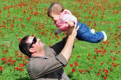 Padre e hija en campo floreciente Imágenes de archivo libres de regalías