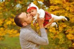 Padre e hija en las hojas caidas otoño en un parque, disfrutando de un día hermoso del otoño Padre joven alegre feliz de la famil fotos de archivo libres de regalías