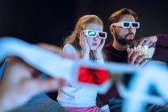 Padre e hija en los vidrios 3d que miran película y que comen las palomitas Imagenes de archivo