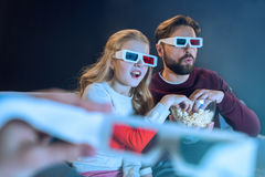 Padre e hija en los vidrios 3d que miran película y que comen las palomitas Imágenes de archivo libres de regalías