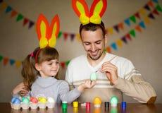 Padre e hija en o?dos del conejito con los huevos coloridos en busket D?a de Pascua Modern Family que se prepara para Pascua fotografía de archivo libre de regalías