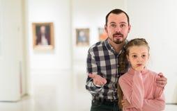 Padre e hija felices con respecto a pinturas en museo Fotografía de archivo