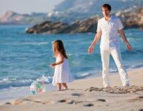 Padre e hija felices de la familia en la playa que se divierte Imágenes de archivo libres de regalías