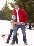 Padre e hija jovenes en nieve con el trineo fotografía de archivo libre de regalías