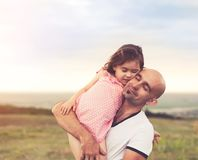 Padre e hija que abrazan en puesta del sol del verano imagen de archivo