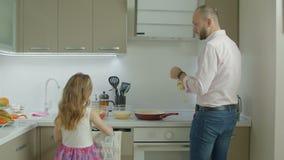 Padre e hija que cocinan el desayuno en cocina almacen de video