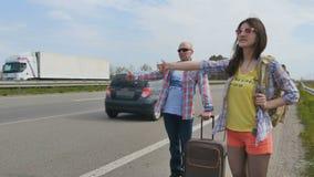 Padre e hija que cogen un coche que hace autostop cerca del camino metrajes