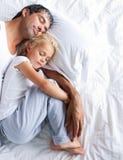 Padre e hija que duermen en cama