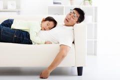 Padre e hija que duermen en el sofá imagenes de archivo