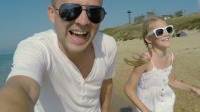 Padre e hija que juegan en la playa metrajes