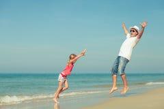 Padre e hija que juegan en la playa en el tiempo del día Imagenes de archivo