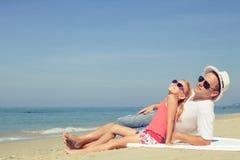 Padre e hija que juegan en la playa en el tiempo del día Foto de archivo