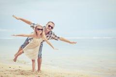 Padre e hija que juegan en la playa en el tiempo del día Imágenes de archivo libres de regalías